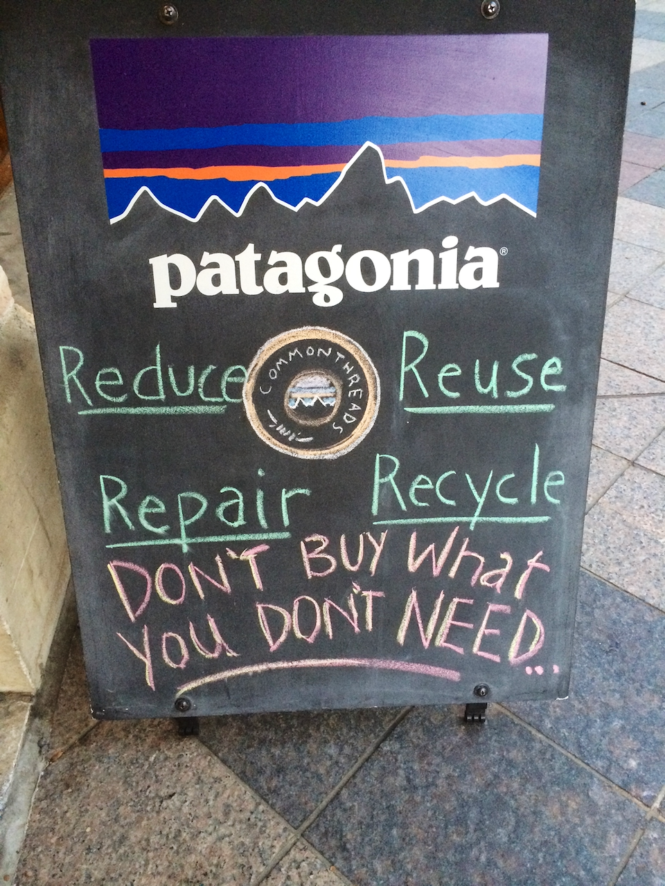 Patagonia sidewalk sign Don't Buy What You Don't Need